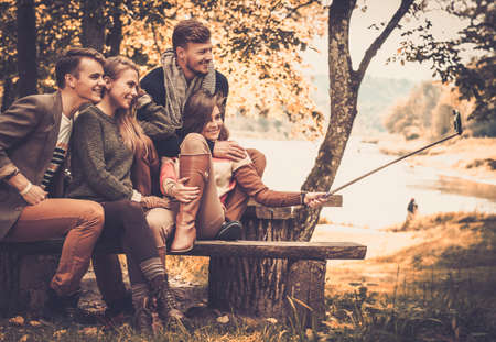 Photo for Cheerful friends in autumn park taking selfie - Royalty Free Image