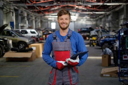 Foto de Cheerful serviceman in a car workshop - Imagen libre de derechos