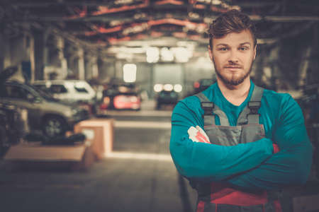 Photo for Cheerful serviceman in a car workshop - Royalty Free Image