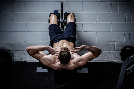 Photo for Muscular man doing exercises for abdominal in The Gym's Studio - Royalty Free Image