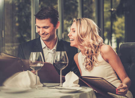 Photo for Cheerful couple with menu in a restaurant - Royalty Free Image
