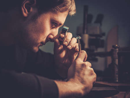 Photo pour Jeweler looking at the ring through microscope in a workshop. - image libre de droit
