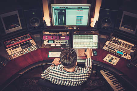 Photo for Sound engineer working at mixing panel in the boutique recording studio. - Royalty Free Image