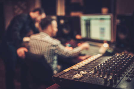 Photo for Sound engineer and producer working together at mixing panel in the boutique recording studio. - Royalty Free Image
