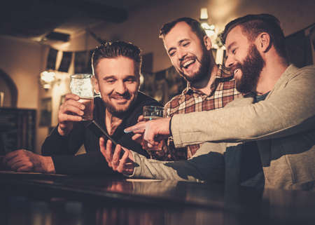 Photo for Cheerful old friends having fun with smartphone and drinking draft beer at bar counter in pub. - Royalty Free Image