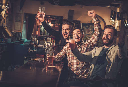 Photo for Cheerful old friends having fun watching a football game on TV and drinking draft beer at bar counter in pub. - Royalty Free Image