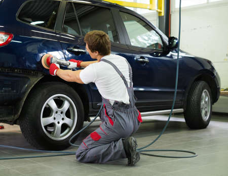 Photo pour Serviceman polishing car body with machine  in a workshop - image libre de droit