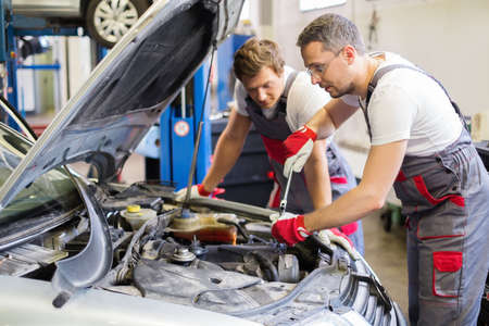 Foto de Two mechanic fixing car in a workshop - Imagen libre de derechos