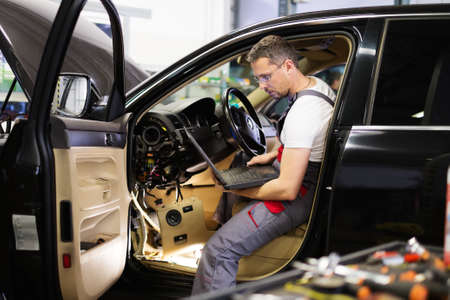 Foto de Serviceman making car diagnostics with laptop in a workshop - Imagen libre de derechos