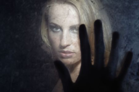 Portrait of the woman indoors behind the dirty glass and touching by the fingers