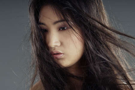 Close-up portrait of the young Asian lady with long hairs