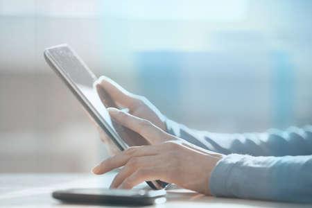 Foto de Hands of woman working with digital tablet behind the glass at office - Imagen libre de derechos