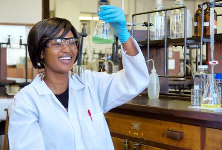 Foto de Happy African female researcher with glass equipment in the lab - Imagen libre de derechos