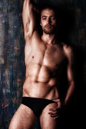 Sexual muscular nude man posing over dark background.