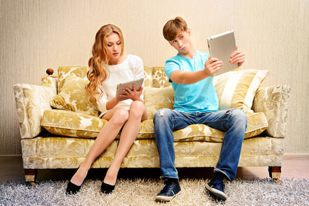 Young woman and a man sitting on a sofa and each of them looks at his own digital tablet.
