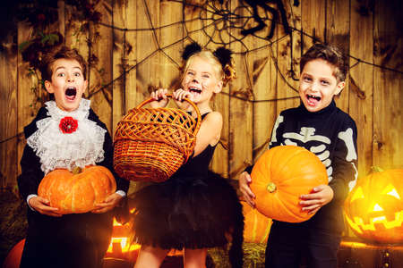 Group of joyful children in halloween costumes posing together in a wooden barn with pumpkins. Halloween concept.