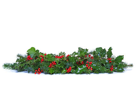 Foto de A traditional Christmas garland made from fresh holly with red berries, green ivy leaves and sprigs of conifer spruce. Isolated on a white background. - Imagen libre de derechos