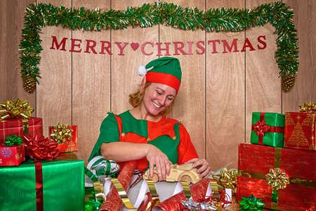 Photo for An elf wrapping Christmas presents in Santa's workshop at the North Pole - Royalty Free Image