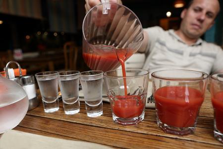 Foto de Man pouring tomato juice in the pub - Imagen libre de derechos