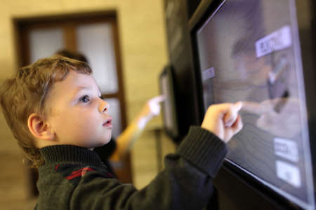 Photo pour Child using interactive touch screen in a museum - image libre de droit