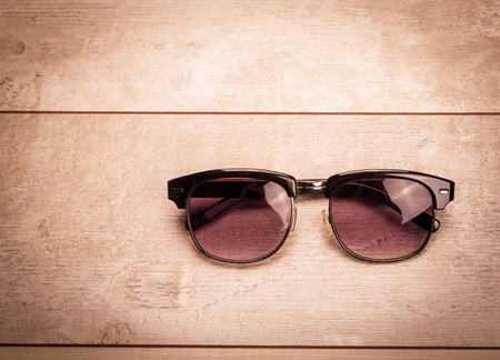 Photo pour black sunglasses on wood floor - image libre de droit