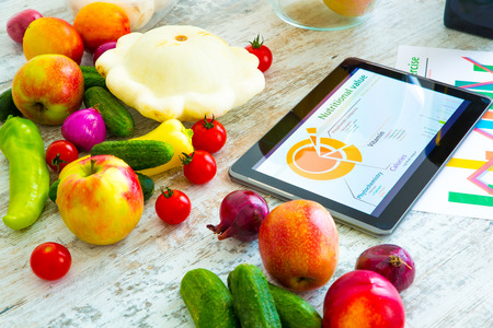 Photo pour Organic food and a Tablet PC showing information about healthy nutrition and phytochemical composition. - image libre de droit
