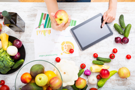 Photo pour Close-up of a young adult woman informing herself with a tablet PC about nutritional values of fruits and vegetables. - image libre de droit