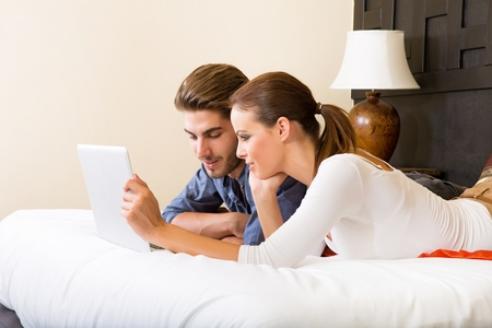 Photo for Young couple using a laptop computer in a asian hotel room - Royalty Free Image