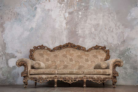 Photo pour Antique sofa against old stucco background - image libre de droit