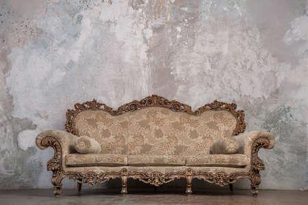 Foto de Antique sofa against old stucco background - Imagen libre de derechos
