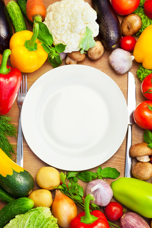 Foto de Fresh Organic Vegetables Around White Plate with Knife and Fork    Vertical Composition - Imagen libre de derechos