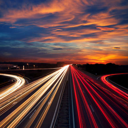 Speed Traffic at Dramatic Sundown Time - light trails on motorway highway at night,  long exposure abstract urban background