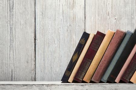 Foto de old book shelf blank spines, empty binding stand on wood texture background, knowledge concept - Imagen libre de derechos