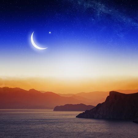 Foto de Eid Mubarak background with moon and stars, holy month, Ramadan Kareem,  beautiful red sunset, mountain silhouettes.      - Imagen libre de derechos
