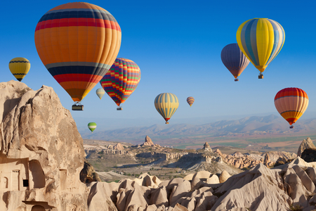 Photo for Amazing attraction - hot air balloons flying above unusual rocky landscape in Cappadocia, Turkey - Royalty Free Image