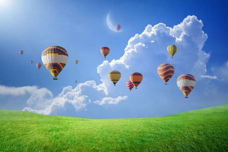Photo for Peaceful heavenly background - colorful hot air balloons rise up into blue sky with white clouds above green field to new moon. Elements of this image furnished by NASA - Royalty Free Image