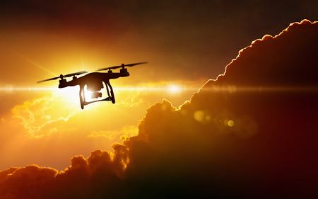 Photo pour Modern technological background - silhouette of flying drone in glowing red sunset sky - image libre de droit