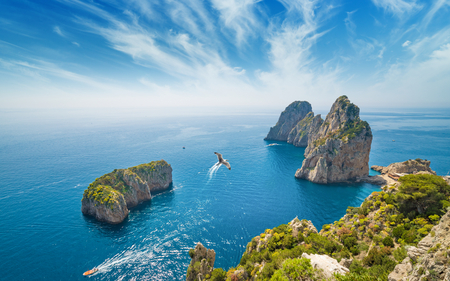 Photo for Aerial view of famous Faraglioni rocks from Capri island, Italy. Sunny summer weather with blue sky and white clouds. - Royalty Free Image