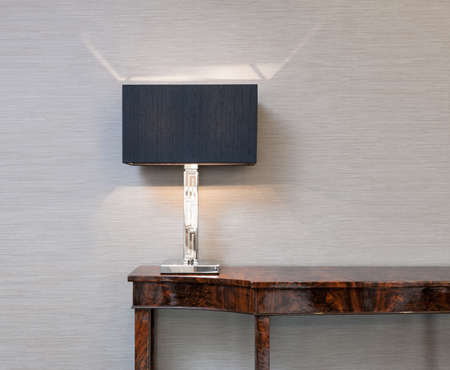 Photo for Sideboard in front of a grey wall with table lamp - Royalty Free Image