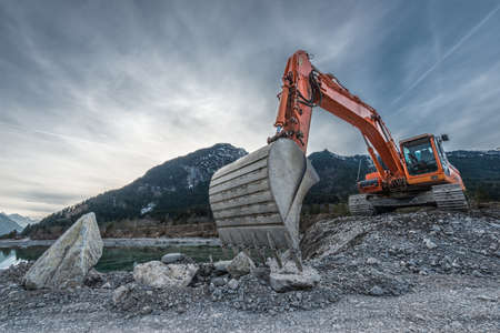 Photo pour big orange digger on gravel heap with big shovel - image libre de droit