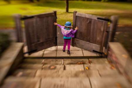 Photo for Young girl opening the wooden gates in the garden - Royalty Free Image
