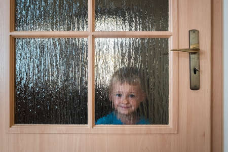 Portrait of a cute little Caucasian boy hiding behind a door with glass windows while playing hide and seek