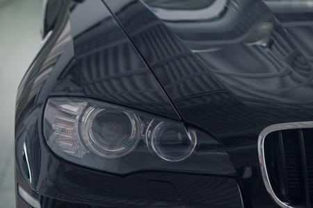 Foto de Cropped photo: a black car front light close-up. business class car - Imagen libre de derechos