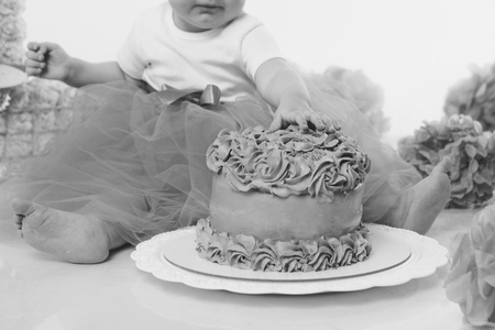 Foto de a little girl eats cake with her hands. The baby was covered in food. isolated white background. birthday party - Imagen libre de derechos