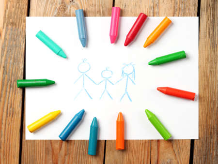 Crayons lying on a paper with children\'s drawing family. Selective focus, top view