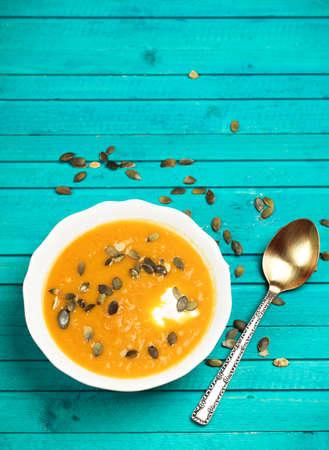 Foto de Still life, food and drink concept. Pumpkin soup with sour cream and seeds on a wooden turquoise table. Selective focus, copy space background, top view - Imagen libre de derechos