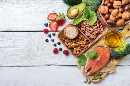 Photo pour Selection of healthy food for heart, salmon fish avocado olive oil pumpkin seeds nuts broccoli green spinach berries on a white rustic wooden table. Copy space background, top view flat lay overhead - image libre de droit