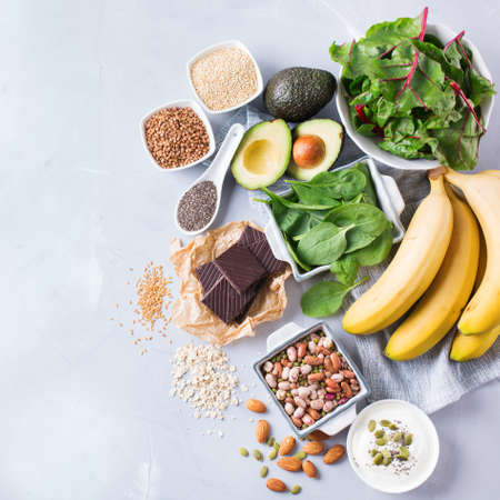 Photo pour Healthy food nutrition dieting concept. Assortment of high magnesium sources. Banana chocolate spinach chard, avocado, buckwheat, sesame chia flax seeds, yogurt, nuts, beans oat. Copy space background - image libre de droit
