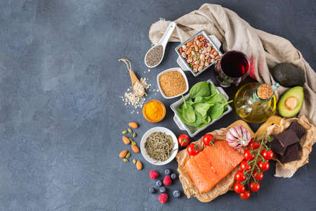 Foto de Balanced diet food concept. Assortment of healthy food low cholesterol, spinach avocado red wine green tea salmon tomato berries flax chia seeds turmeric garlic nuts olive oil. Copy space background - Imagen libre de derechos