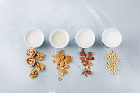 Photo for Food and drink, health care, diet and nutrition concept. Assortment of organic vegan non diary milk from nuts in glasses on a kitchen table. Top view flat lay background - Royalty Free Image
